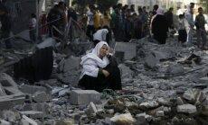 Palestinietė sėdi tarp griuvėsių Rafah pabėgėlių stovykloje