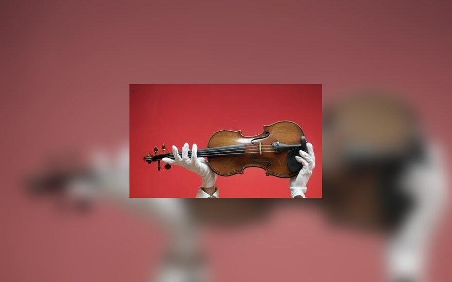 """""""Christie's"""" aukciono darbuotoja laiko Stradivarijaus smuiką. 1729 metais pagamintą instrumentą balandį tikimasi parduoti už ne mažiau kaip 1,5 mln. JAV dolerių."""