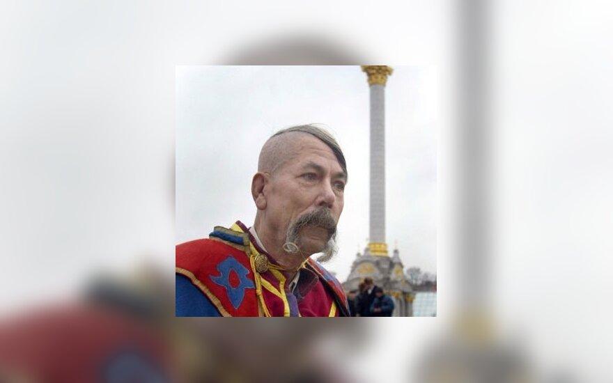 Vyras, apsirengęs tradiciniais Ukrainos kazoko drabužiais, eina pro Nepriklausomybės paminklą Kijeve.