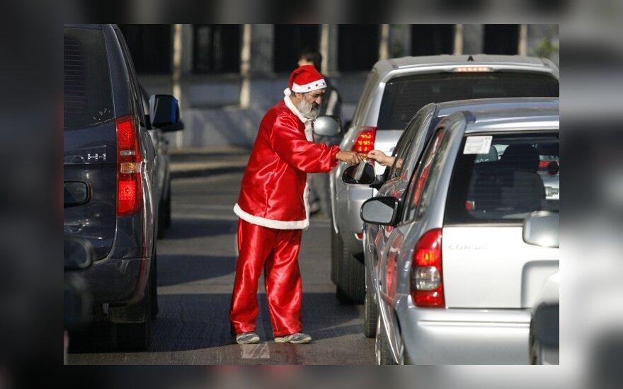 Vyras, apsirengęs kaip Kalėdų senelis, Santjago gatvėje prašo pinigų.