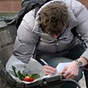 Vyras rašo, pasidėjęs gėlę šalia