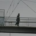 Žmogus eina pėsčiųjų tiltu virš geležinkelio