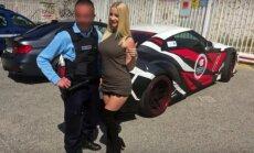 Policijos pareigūnas fotografuojasi su Mareike Fox prie jos Nissan GT-R