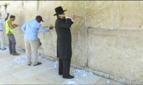 Iš Raudų sienos plyšių traukiami žmonių palikti rašteliai Dievui