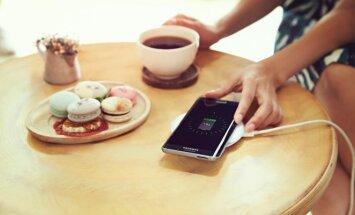 Išmanusis telefonas kraunasi ant stalo