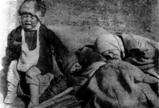 Bado išsekintas vaikas greta iš bado mirusios šeimos