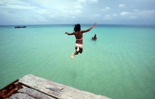 Šuolis į vandenį viename iš Kukurūzų salų paplūdimių
