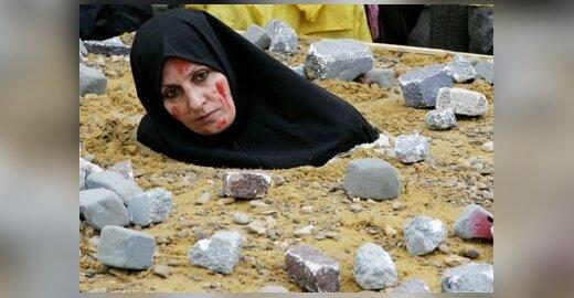 Iranietė moteris, vaizduodama akmenimis užmuštą auką, protestuoja Briuselyje, kur renkasi ES užsienio reikalų ministrai svarstyti Irano pasiūlymo bendradarbiauti dėl branduolinės programos.
