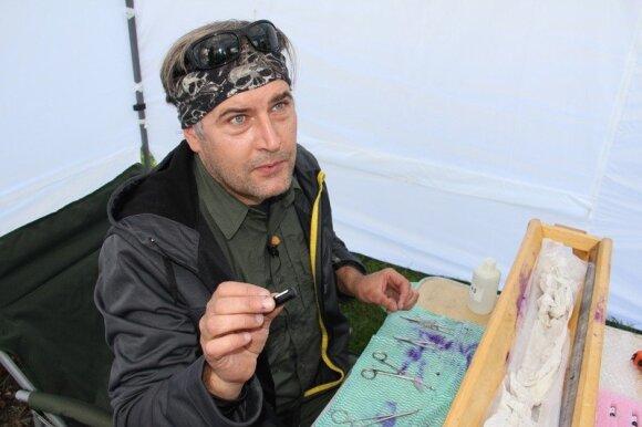 Mokslininkas demonstruoja siųstuvą, kuris implantuojamas į žuvį