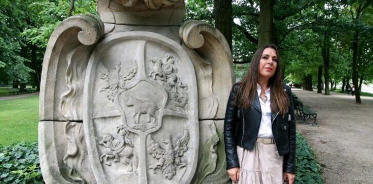 Rašytoja Kristina Sabaliauskaitė prie karaliaus Stanislovo Augusto Poniatovskio herbo, ženklinančio vieną Lazienkų parko prieigą