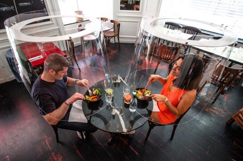 Žmonės Prancūzijos restorane valgo po plastikiniais skydais