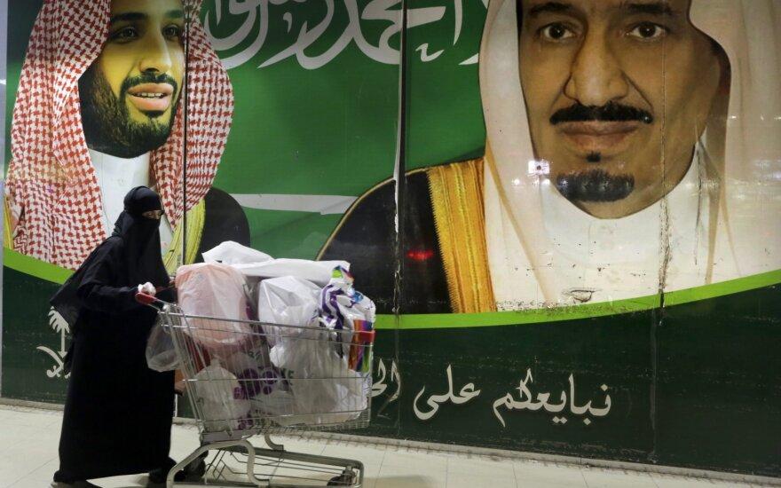 Moteris šalia princo Mohammed bin Salman ir karaliaus Salman atvaizdų