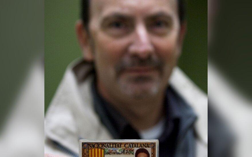 Nuo Ispanijos atsiskirti norintis  katalonietis rodo simbolinę regiono tapatybės kortelę.