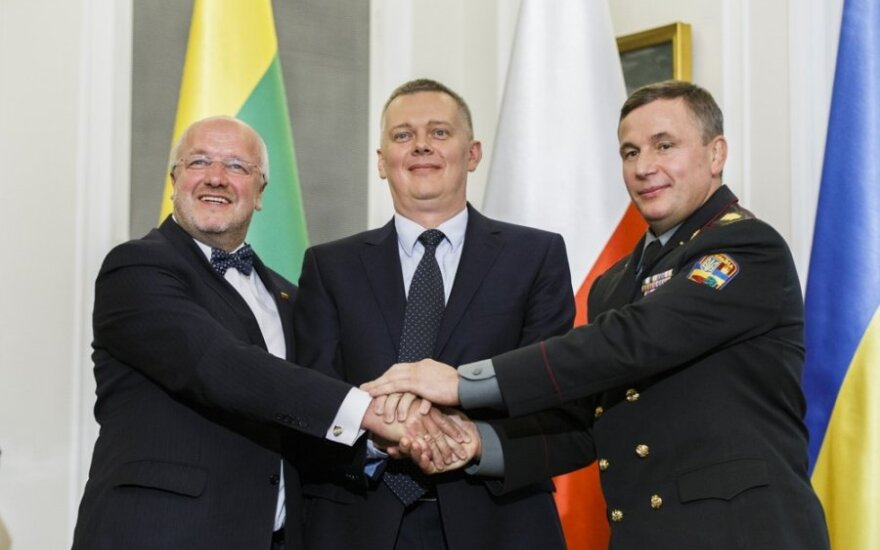 Ukrainian Defense Minister Valeriy Heletey (R), Polish Defense Minister Tomasz Siemoniak (C) and Lithuanian Defense Minister Juozas Olekas shake hands after signing an agreement on the creation of a joint military brigade on Sept. 19 in Warsaw.