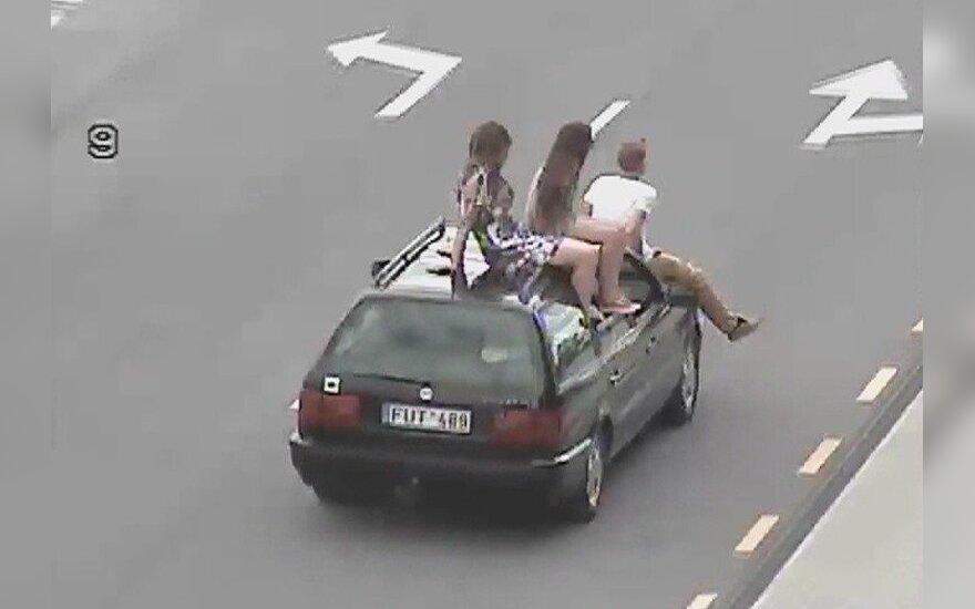 Pasivažinėjimas Klaipėdoje: vaikinas ant variklio dangčio, dvi merginos - ant automobilio stogo