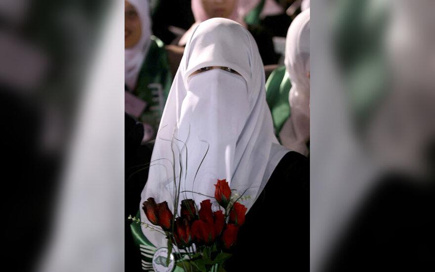Balta čadra apsigobusi palestinietė – nuotaka stovi su rožių puokšte masinėje vedybų ceremonijoje Nablus mieste, kur iškart buvo sutuoktos 226 poros.