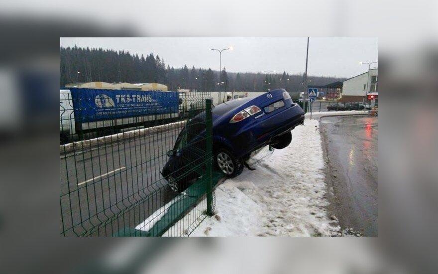 """Po autobuso smūgio, """"Mazda 6"""" išvertė Medininkų punkto tvorą"""