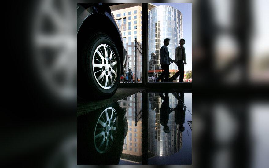 Kinijoje praeiviai eina pro automobilių ekspoziciją Pekine.