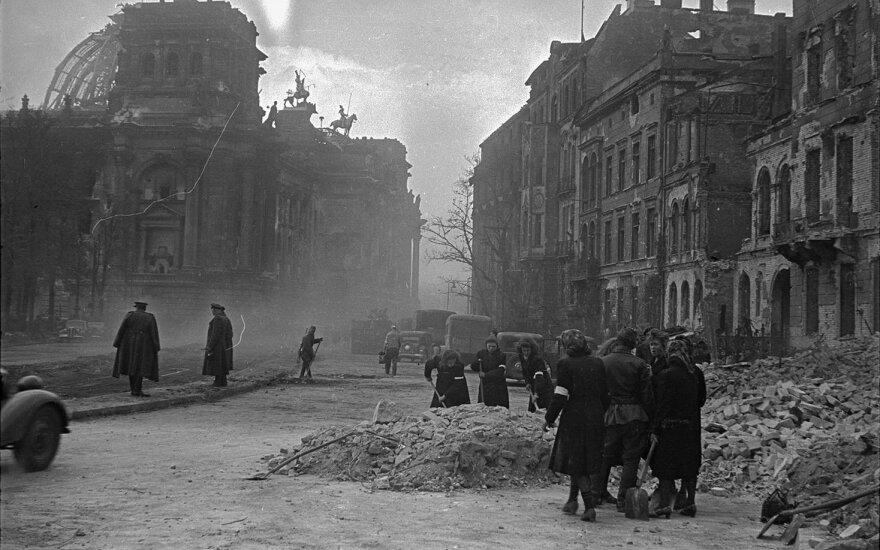 Vokiečių moterys ardo griuvėsius prie Reichstago. Tolėliau matyti sovietų kariškiai.