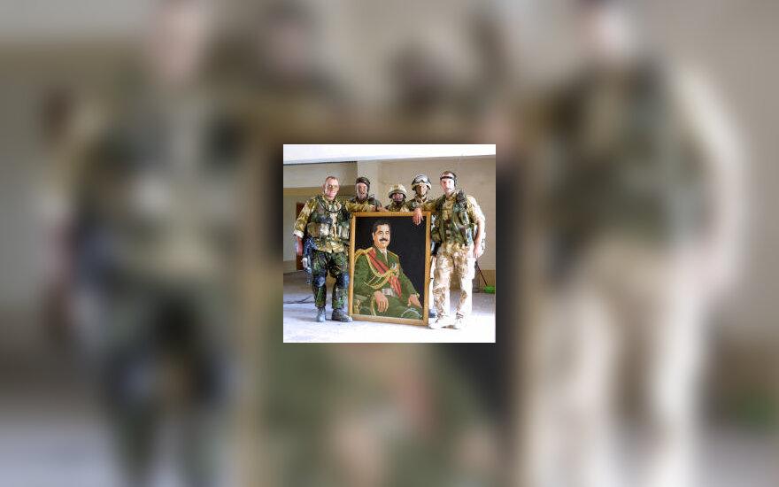 Britų kariai pozuoja prie S.Husseino portreto