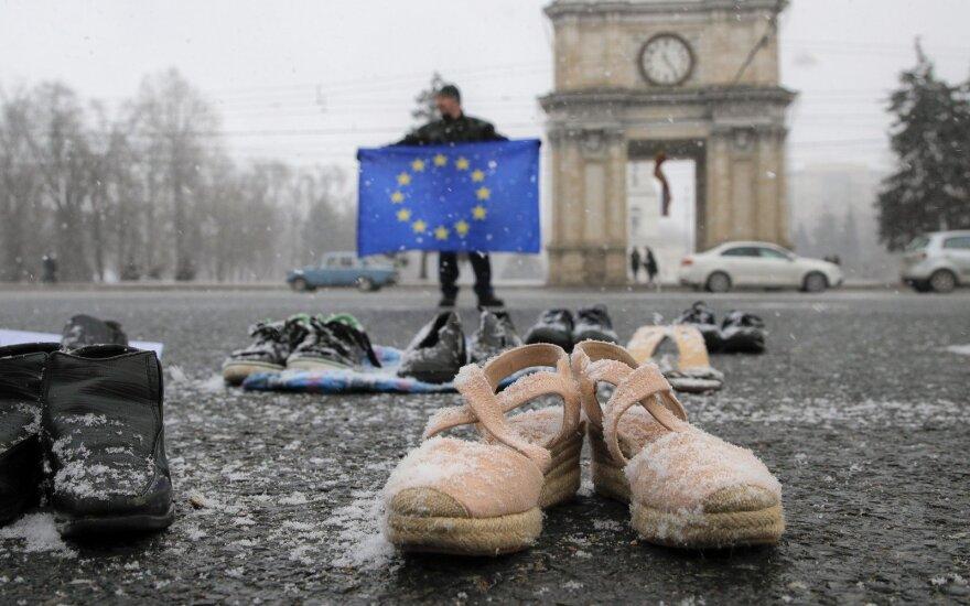 Vyras su ES vėliava dėl prastų pragyvenimo sąlygų protestuoja Kišiniove. Batai simbolizuoja išvykusius Moldovos emigrantus