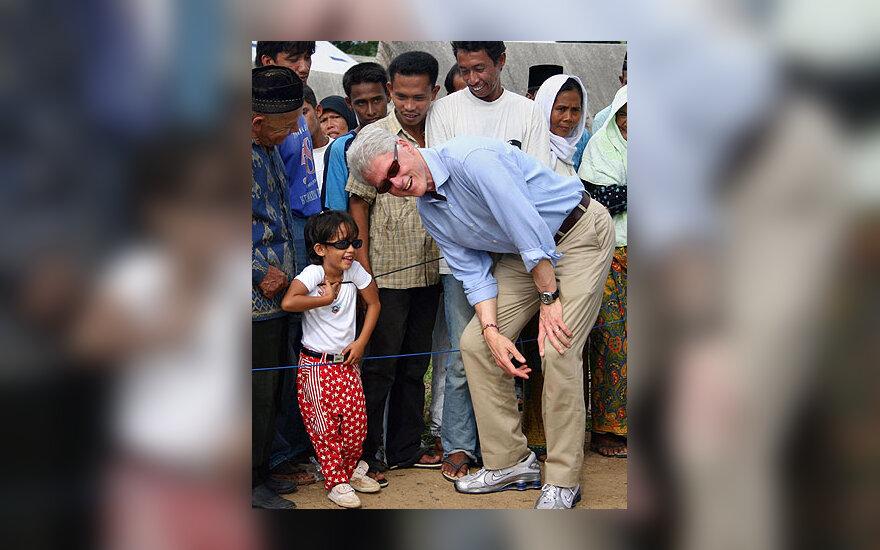 Buvęs JAV prezidentas Billas Clintonas juokauja su vietine mergaite savo vizito Indonezijoje metu.