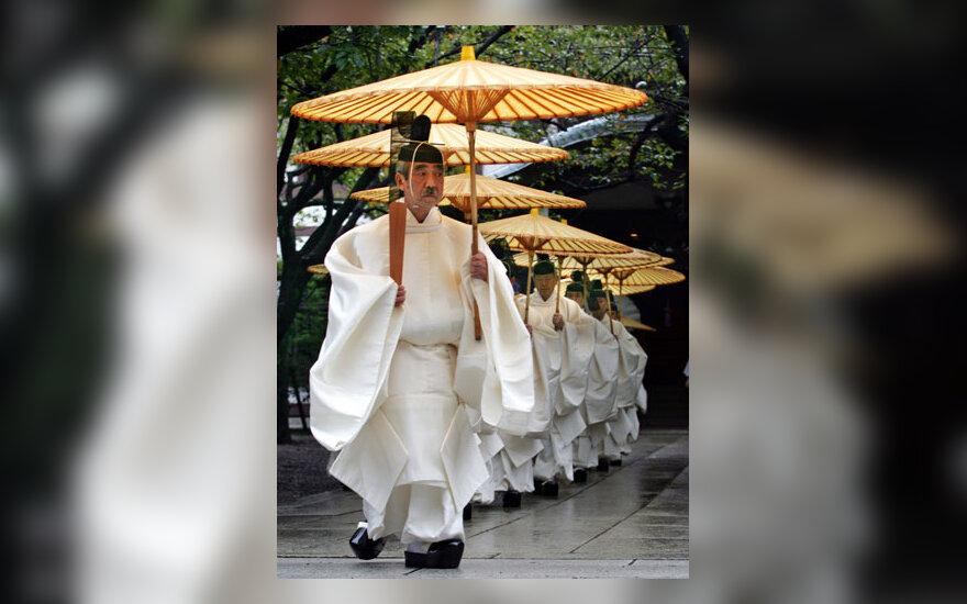Japonų Šinto dvasininkai laikydami popierinius skėčius eina per lietų rudens festivalyje Tokijuje.