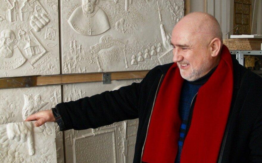 """Autorius savo dirbtuvėje prie žymiausio savo kūrinio -Telšių  Šv. Antano Paduviečio Katedros durų kuriamų reljefų, darbo eigoje (""""Beigelių krautuvėlės"""" nuotr.)"""