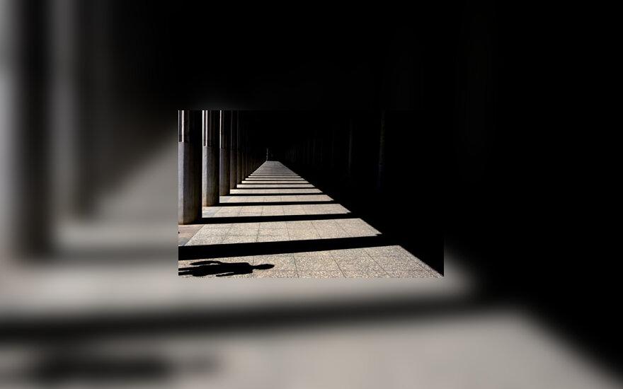 Turisto šešėlis šalia Akropolio kolonų šešėlių Atėnuose.