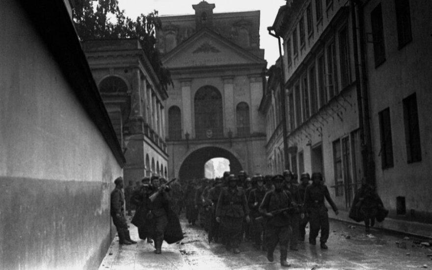 Vokiečių belaisviai, su ginkluota palyda vedami pro Aušros vartus. Greičiausiai fotografuota 1944 m. liepos 13 arba 14 d., nes tomis dienomis lijo, o nuotraukoje gatvės grindinys šlapias.