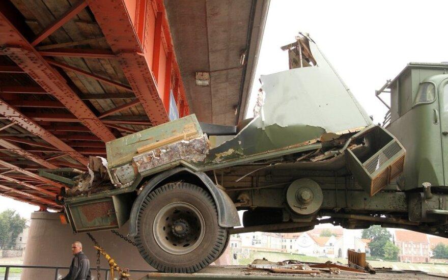 """Kariškių sunkvežimis netilpo po tiltu, krovinys virto ant pravažiuojančio """"Peugeot"""""""