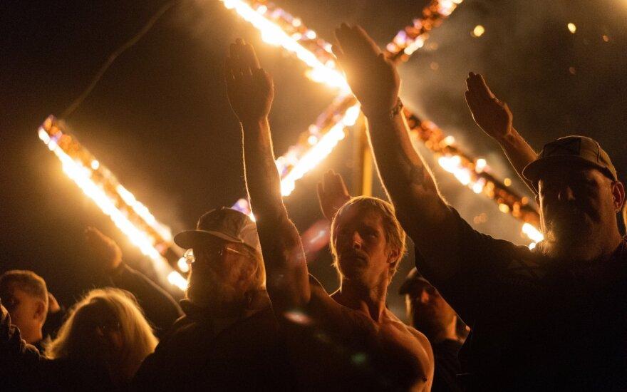 Nacionalsocialistinio judėjimo rėmėjai skiria nacių sveikinimus dalyvaudami svastikos deginime Džordžijos valstijoje, JAV