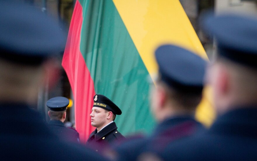 Soldier next to the Lithuanian flag