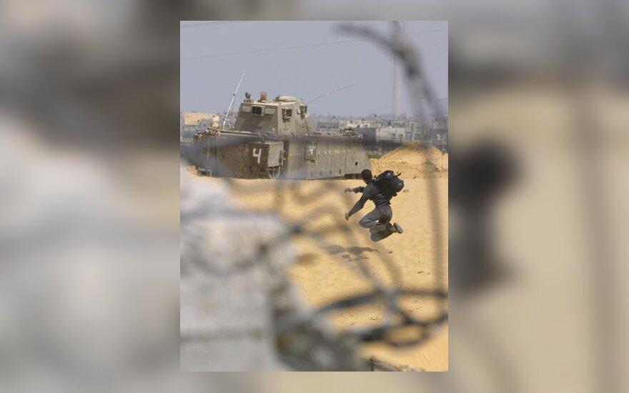 Palestiniečių jaunuolis meta akmenį į Izraelio armijos tanką