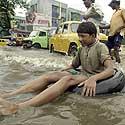 Berniukas plaukia ant pripučiamos padangos potvynio užtvindyta Kalkutos gatve.