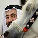 Jungtinių Arabų Emyratų šeichas Bin Mohammadas Al Kasini šypsosi šalia savo žirgo.