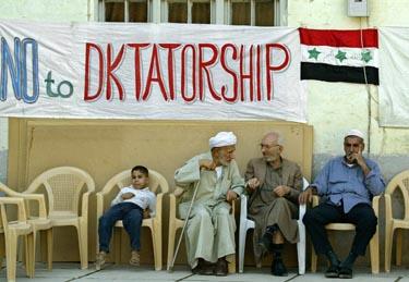 """Irakiečiai sėdi po plakatu """"Ne diktatūrai"""", Irakas"""