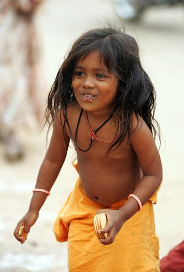 Be tėvų likusi maža indė mergaitė džiaugiasi sausainiais.