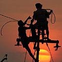 Indų darbininkai tvarko elektros kabelius