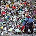 Žmogus stovi prie didelės plastikinių butelių krūvos