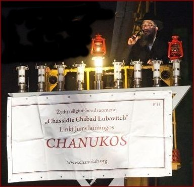 For the 22nd year running, Rabbi Sholom-Ber Krinsky of Boston will be hoisted up on a crane high above Gedimino (at Kudirkos Square, opposite the Novotel) this Thursday 10 Dec. at 6 PM, to lead the lighting of the men